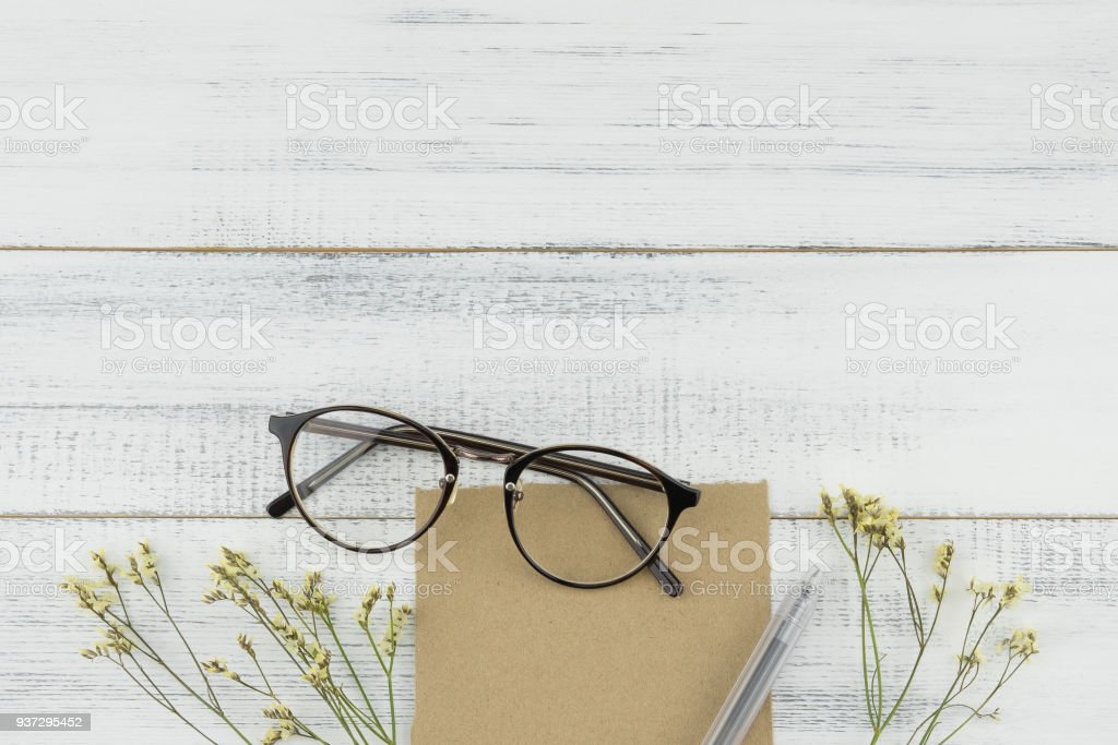 Blank brown card, pen and eyeglasses decorated with yellow limonium caspia flowers stock photo