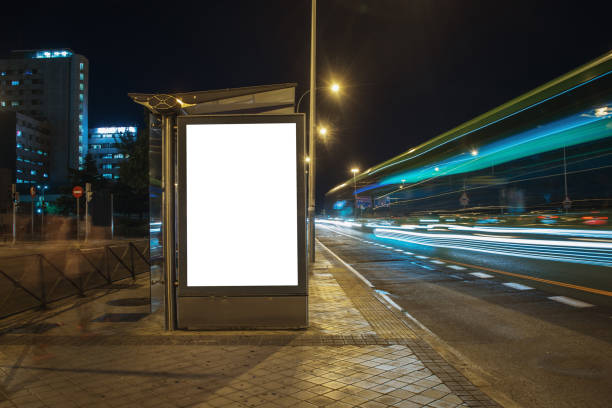 Blank bus stop with billboard at night stock photo