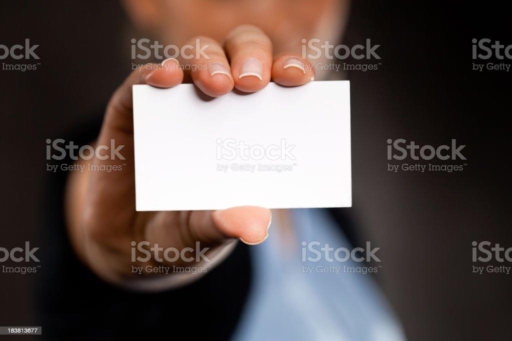 Blank business card in businesswoman's hand on dark background stock photo