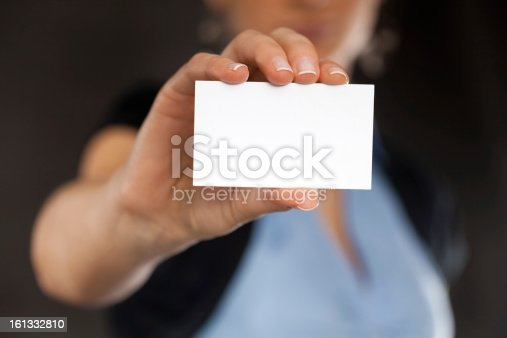Close-up of a blank business card in businesswoman's hand. Dark background. You can put your text.