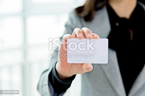 Businesswoman showing a blank business card.