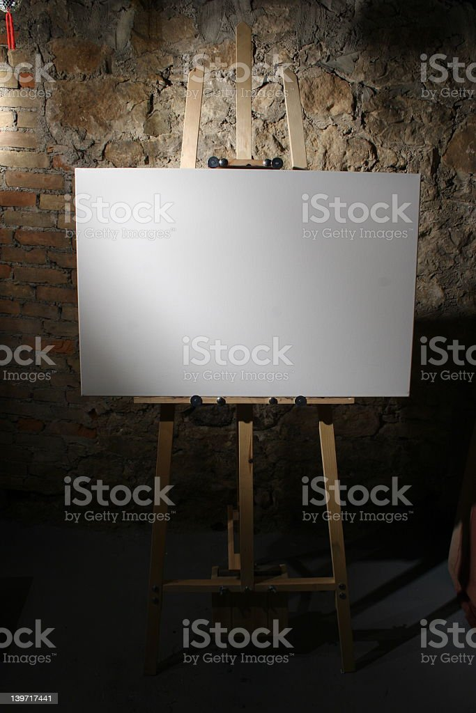 A blank canvas on an easel against a brick wall royalty-free stock photo