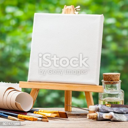 istock Blank canvas on easel, artistic paintbrushes, tubes of oil paint 507477566