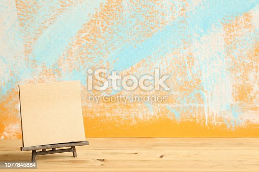 671393252istockphoto Blank canvas on wooden easel with abstract colorful painted background. Art concept 1077845884
