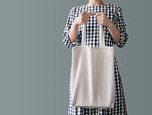 A woman in a plaid cotton dress is holding a reusable white shopping bag