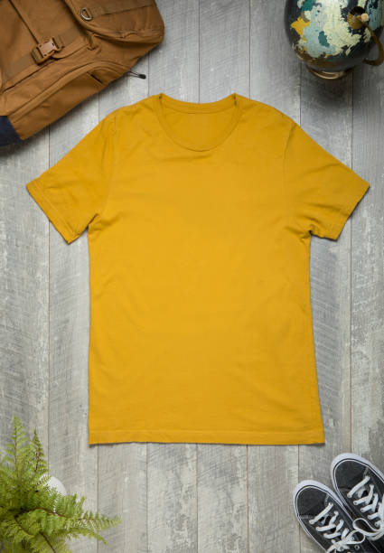Blank canvas yellow T-shirt on wood background with props stock photo