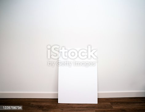 1062226450 istock photo Blank canvas,poster or board against white wall on pvc floor in modern interior, empty room space for text 1225756734