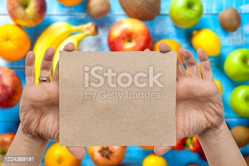 Woman holding empty blank card for messages with fresh fruit in background