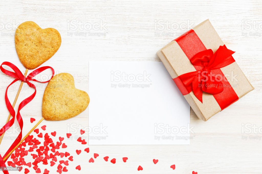 Blank card, gift wrapped in kraft paper, two homemade cookies stock photo