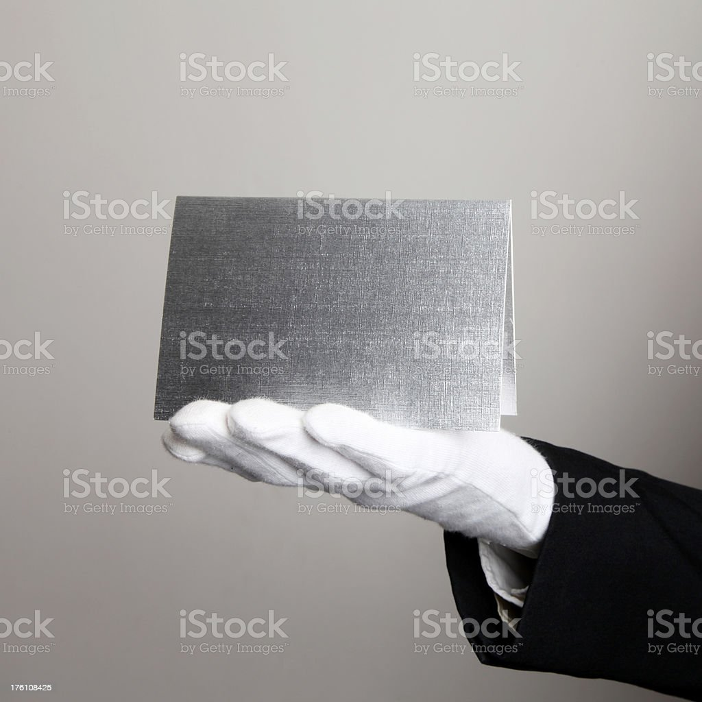 blank card held by butler with white glove royalty-free stock photo