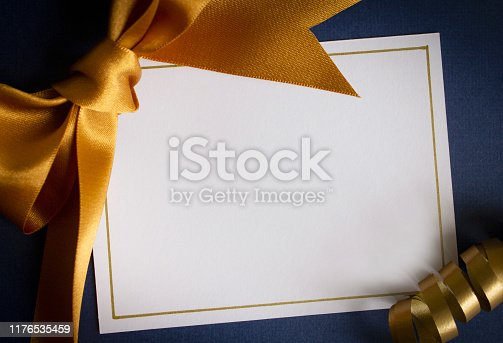 A blank card with gold ribbons on a blue background