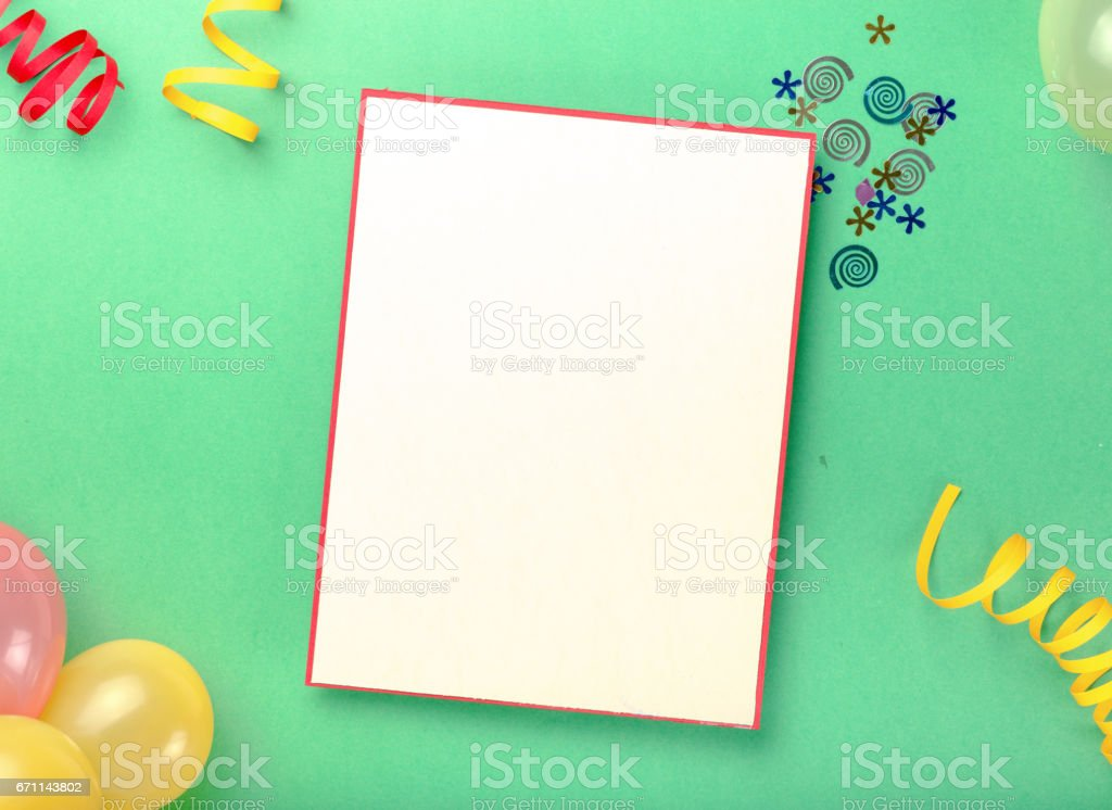 Blank card with various party confetti, balloons and streamers on a green background stock photo