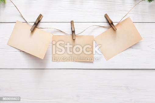 istock Blank cards on rope on light wall background 865655622