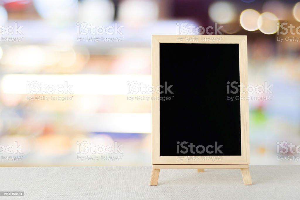 Leere Tafel steht auf Sack Tischtuch über Unschärfe Store mit Bokeh Hintergrund, Raum für Text, mock-up Produkt Display montage – Foto