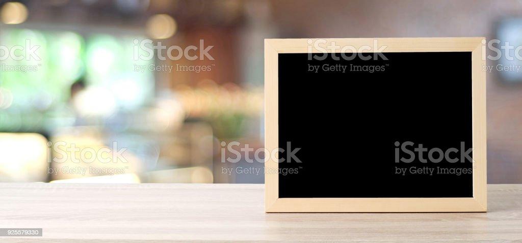 Leere Tafel stand am Tisch über Unschärfe Store mit Bokeh Hintergrund, Raum für Text, mock-up Produkt Display montage – Foto