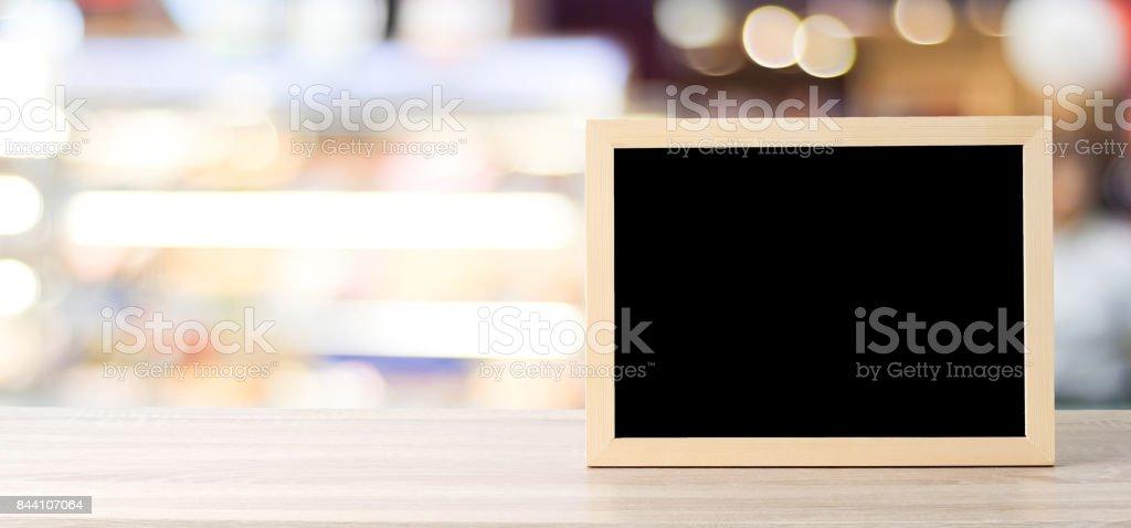 Leere Tafel stand auf Holztisch über Unschärfe Café mit Bokeh Hintergrund, Banner, Raum für Text, mock up, Lebensmittel- und Anzeige montage – Foto