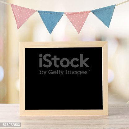 istock Blank chalkboard standing over colorful party flags and blur background with copy space for text, new year and festival card, banner 673272800