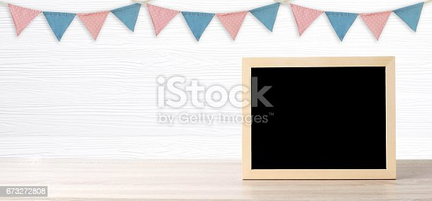 istock Blank chalkboard standing over colorful party flags hanging on white wood background with copy space for text, new year and festival card, banner 673272808