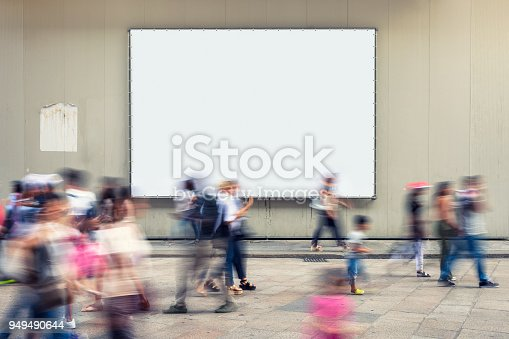 People in motion walking along a city street in front of a large blank poster.