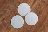 Three round white coasters on wood background. 3d illustration