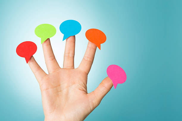 Blank colourful speech bubbles on fingertips stock photo