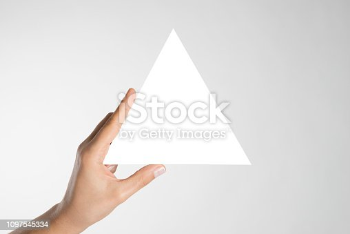 Hand is holding blank white triangle.