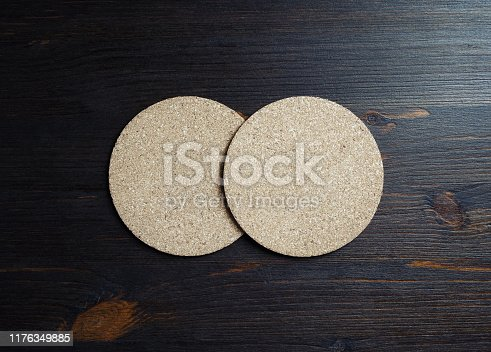 Two blank cork beer coasters on wood table background. Flat lay.