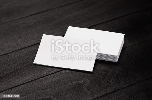 istock Blank corporate identity business card and stack on black stylish wood background with blur, template. 696503838