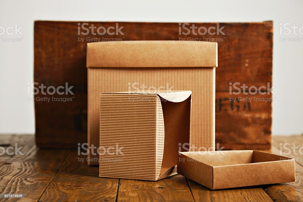 Blank corrugated cardboard boxes with vintage wooden box stock photo