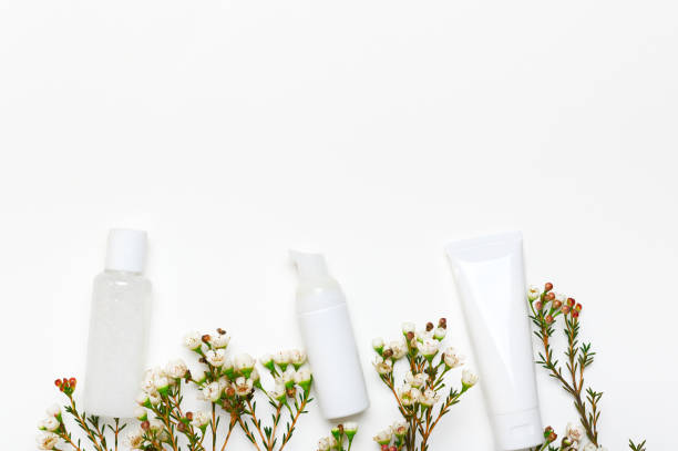 Blank cosmetic bottles mockups with flowers empty background. Makeup remover, lotion dispenser, cream tube white packages. Skincare products and Geraldton waxflower on backdrop. Facial moisturizers stock photo