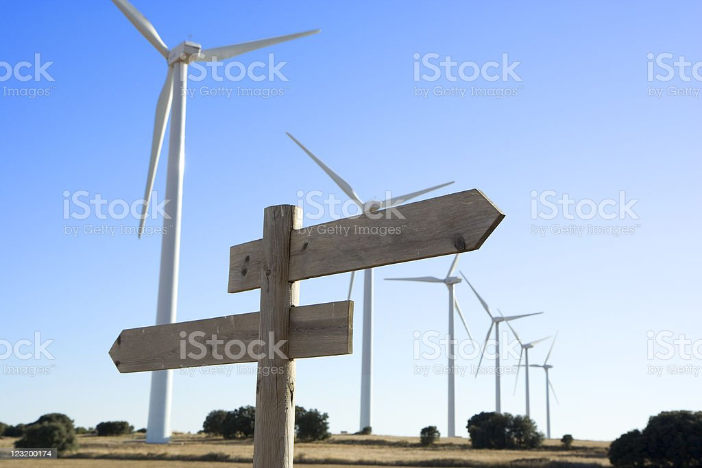 Blank cross road sign with windmills in the background royalty-free stock photo