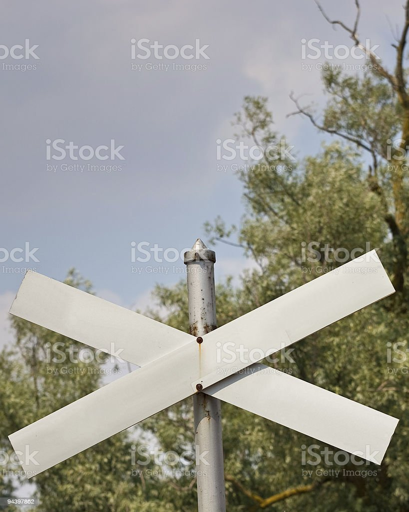 Blank crossing sign against trees and sky royalty-free stock photo