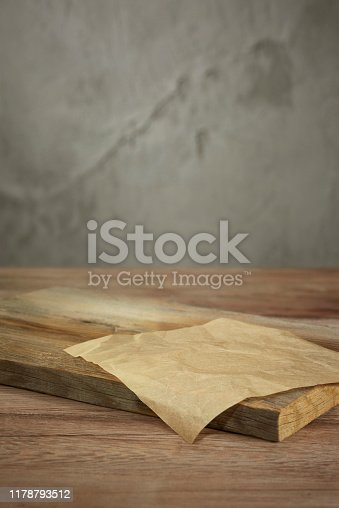 empty cutting board  on table setting in front of a concrete wall