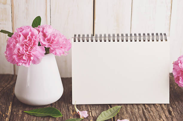 Blank Desk calendar with pink carnation flower stock photo