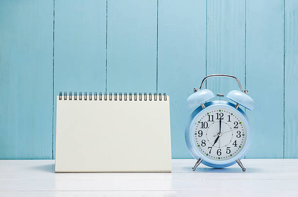 Blank desk calender with vintage Alarm clock stock photo