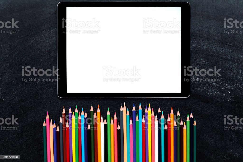 Blank digital tablet and colored pencils on blackboard stock photo