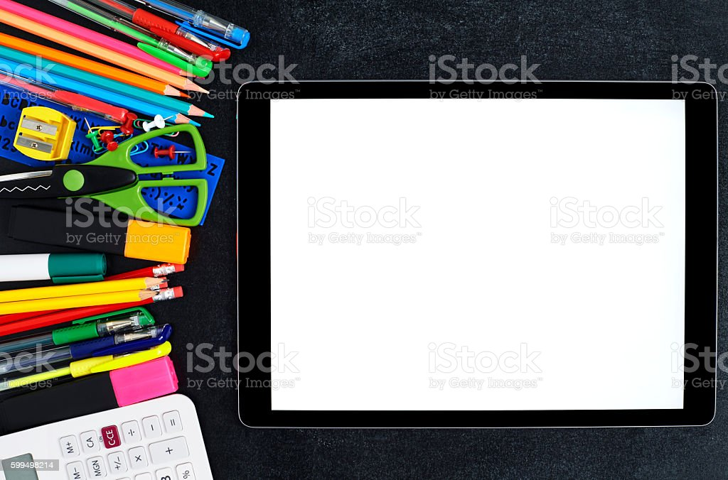 Blank digital tablet by school supplies on blackboard stock photo