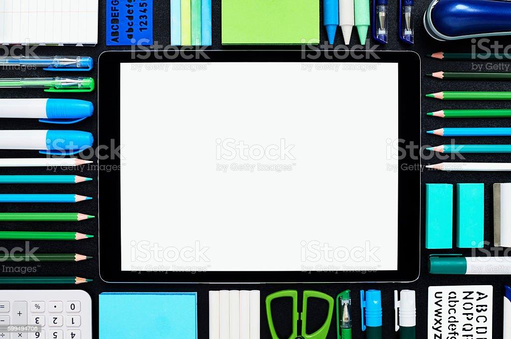 Blank digital tablet surrounded by school supplies on blackboard stock photo