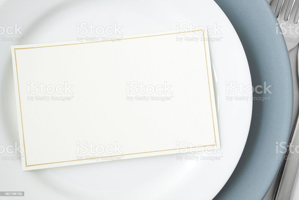 Blank dinner invitation centered on a white entree plate royalty-free stock photo