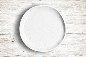 Top view of empty white food dish on a wooden background.