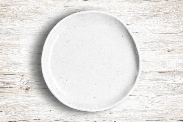 Blank Dish Top view of empty white food dish on a wooden background. ceramics stock pictures, royalty-free photos & images