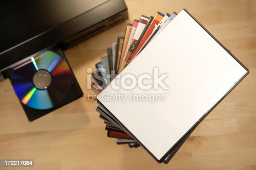 pile of dvds near dvd player with dvd on open tray