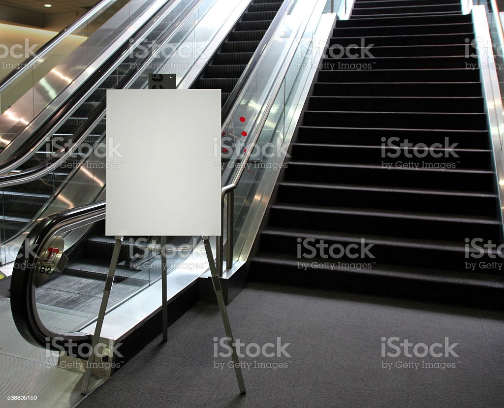 Blank easel sign at the base of an escalator stock photo