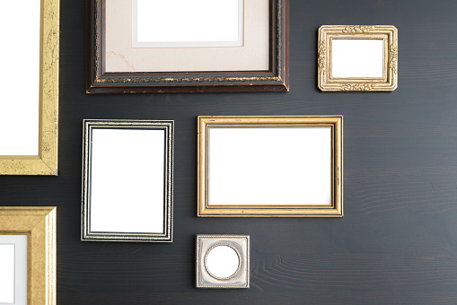 Blank empty frames on dark wooden background.