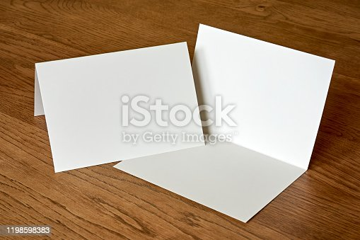 Blank empty greeting card with open envelope mock up on dark wooden background. For use as a Christmas, birthday, wedding or celebration background template.