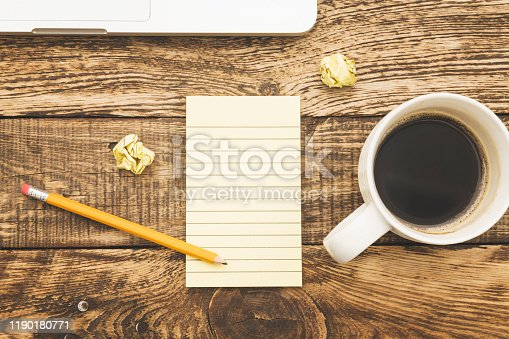 862672018istockphoto Blank empty paper with pencil and cup of coffee 1190180771