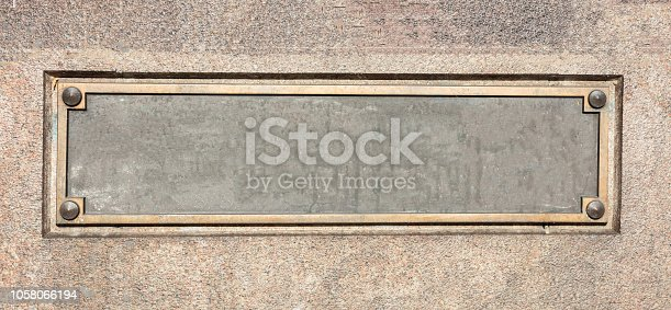 Blank empty sign with brass frame on stone wall facade, banner, copy space