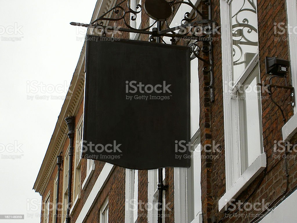Blank English pub sign hanging from wall stock photo