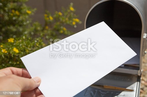 A person retrieves a blank envelope from the mailbox. Envelope can be edited by the user.