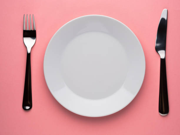 Blank flat plate, knife, fork on a color pink table, top view. stock photo